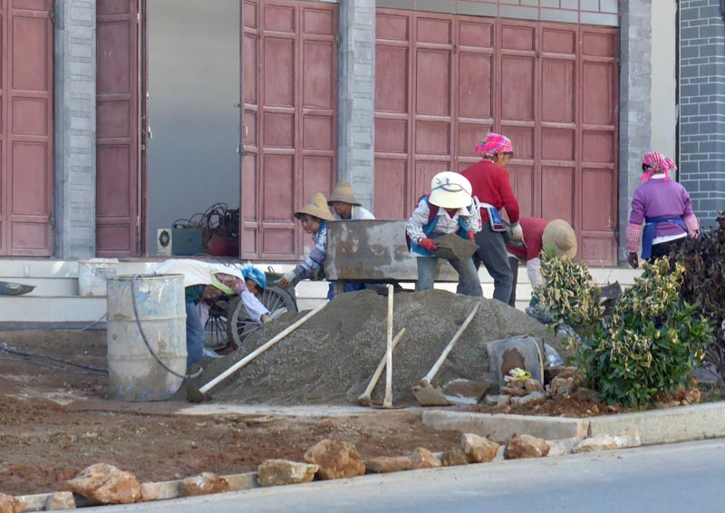 kina22 Husen byggs av kvinnorna, blandar, kör tegel och murar.